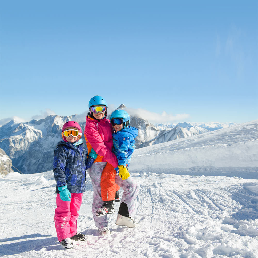 Happy family enjoying winter vacations in mountains . Ski, Sun, Snow and fun