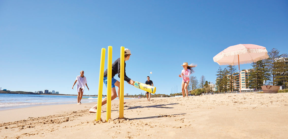 Kids playing cricket on a sunshine coast beach in Queensland, Australia