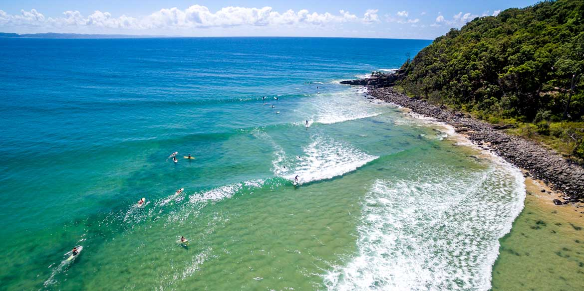 surfing at Noosa Heads Beach