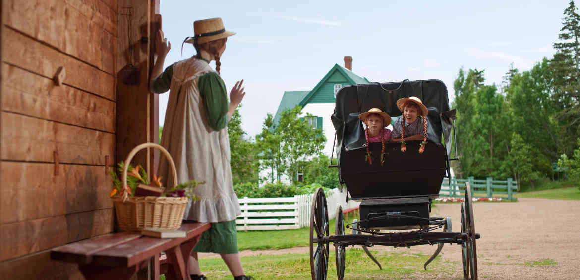 A Parks Canada interpreter dressed as Anne of Green Gables waves to young visitors in a horse buggy at Green Gables Heritage Place