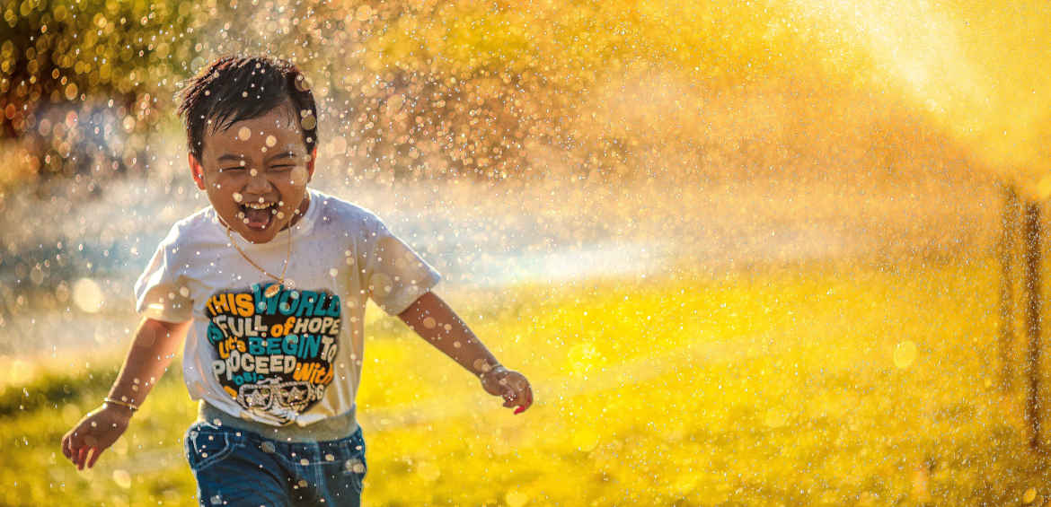 kid running through sprinklers