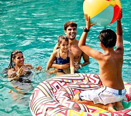 Family playing in the pool at Mövenpick Resort & Spa Jimbaran Bali