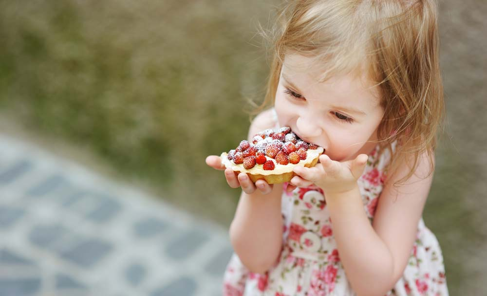 Little girl eating a strawberry tart outdoors