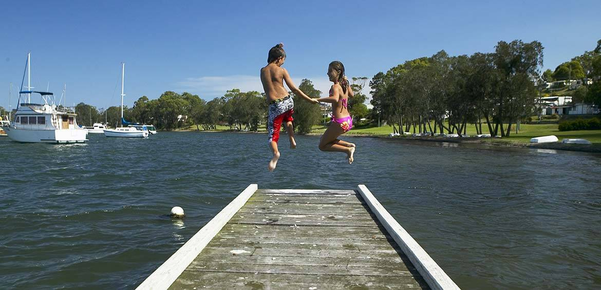 Kids jumping off at jetty in Lake Macquariue
