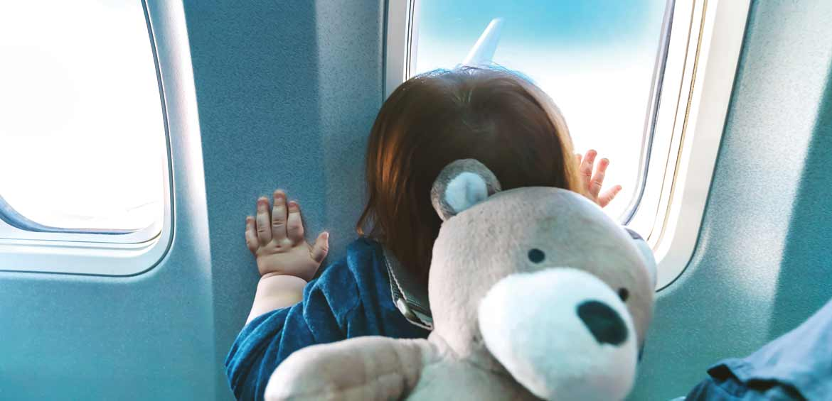 Toddler looking our plane window. Image © Shutterstock/TierneyMJ