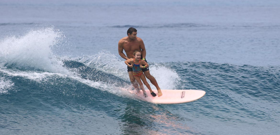 Dad and daughter surf