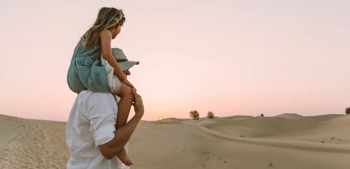 Little girl sitting on dad's shoulders and looking at the sunset in the desert