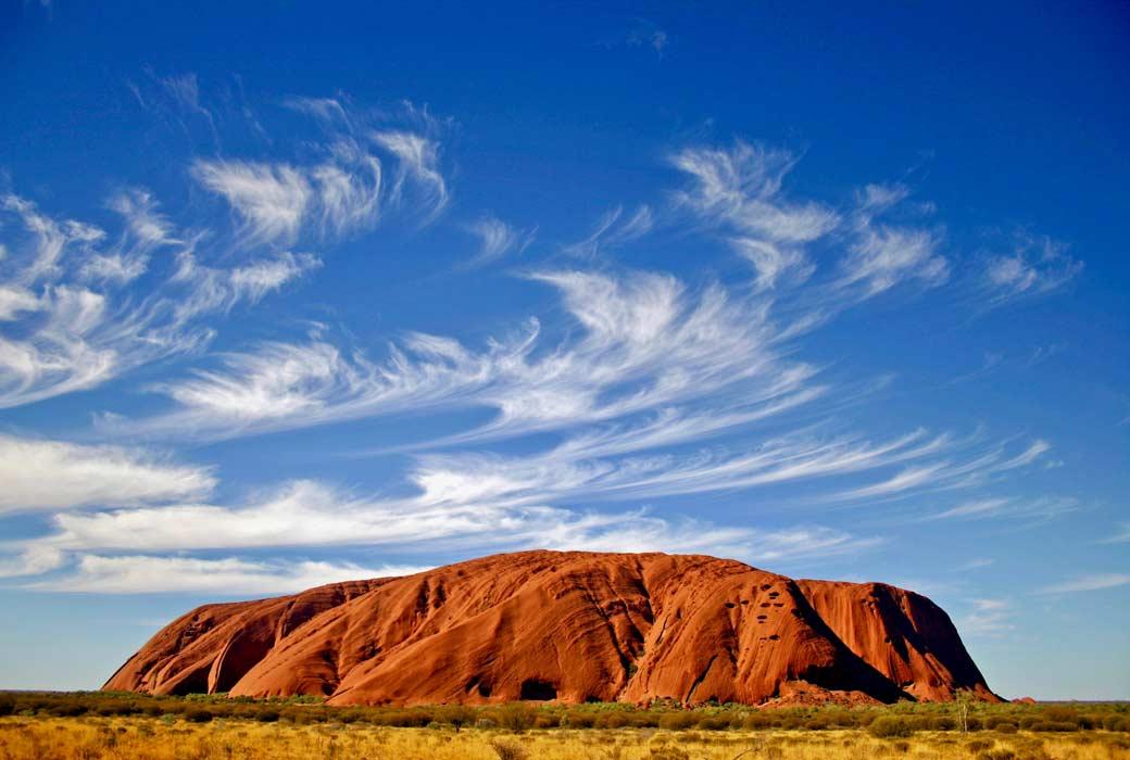 NT border open Uluru Ayers Rock with wispy clouds.