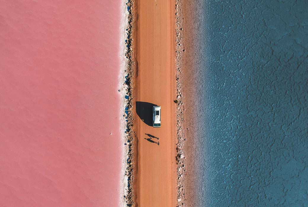 A camper van parked in the middle of one of the most beautiful pink and blue lakes - Lake Macdonnell, South Australia.