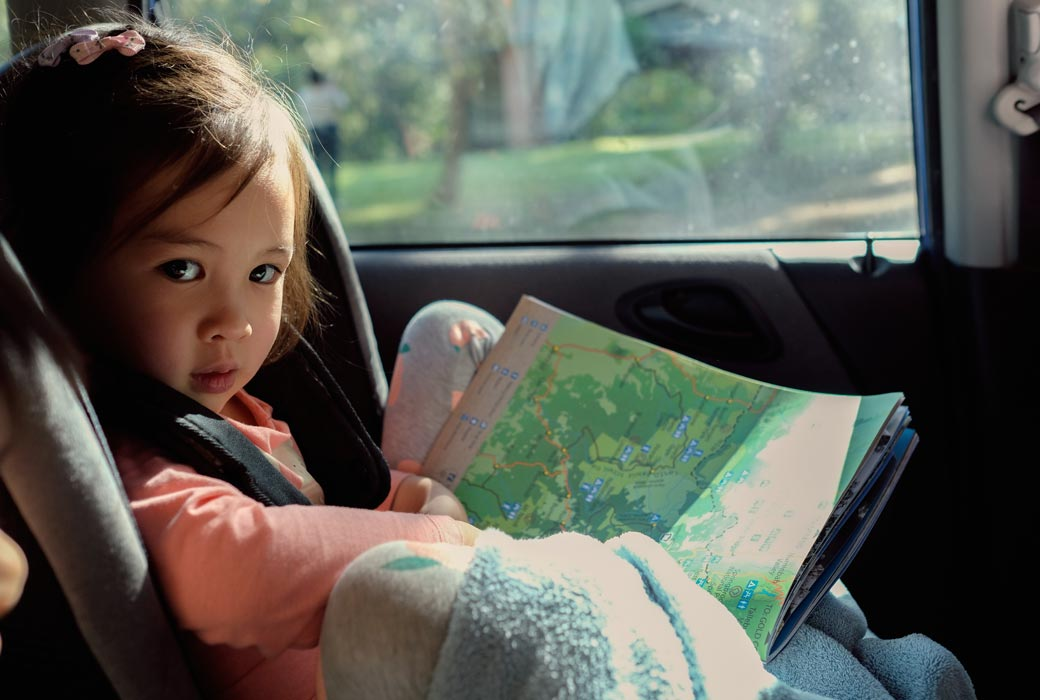 Little girl reading a map in the car